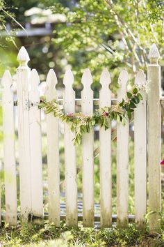 A garland-clad white picket fence #smpliving | Photography by Jade   Matthew Take Pictures / http://www.jadeandmatthew.com |  http://www.smpliving.com