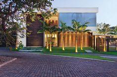 Uma aura receptiva envolve a fachada graças ao equilíbrio visual entre a rusticidade da parede em tijolos ingleses da Palimanan (Vallori) e da porta de madeira de demolição com a leveza dos panos de vidro (Vidromex). O paisagismo com palmeiras é de Mendo Barreto e as persianas, no  segundo piso, são da Hunter Douglas (Finestri).