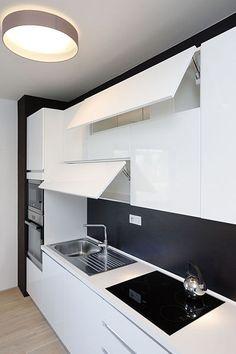 Zajímavý 3D efekt vznikl u kuchyňské linky díky sádrokartonovému obložení ve stejném odstínu jako tmavý obklad nad pracovní deskou. Detail zvýrazní bíle lakovaná dvířka s bezúchytovým systémem push-pull, která jsou vizuálně propojená do tvaru větrníku.