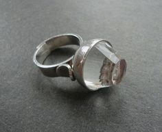 "An amazing sterling silver modernist ring by Elis Kauppi for Kupittaan Kulta. This unusual ring has a floating bead under the faceted crystal, which was very hard to photograph. Ring is currently a 7 1/2 but is adjustable. Sits 5/8"" above the shank. Marked with the anvil, 925S and Finland."