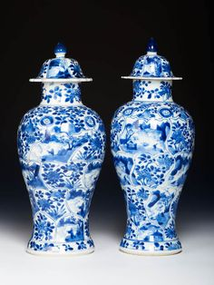 Two Chinese export porcelain baluster vases with moulded panels and covers<br/>Decorated in under-glaze cobalt blue (Qinghua) with flowers and landscapes. c. 1700, Kangxi reign, Qing dynasty,h. 28,5 cm, 11 in