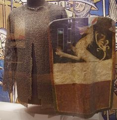 European (German) riveted mail hauberk, 15th century, shown with a pavise (shield): Decorated with arms of Enns, Austria, mid 15th century. Frazier International History Museum.