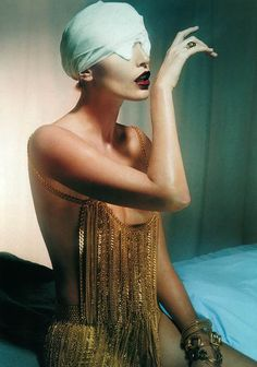 """She's """"draped"""" in gold chains with bandages covering 50% of her head. Must be art."""