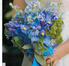As a color scheme, the couple chose green and white to complement the countryside that would be surrounding them, though the bridesmaid dresses were a brilliant blue, a color that was picked up in Carly's bouquet.