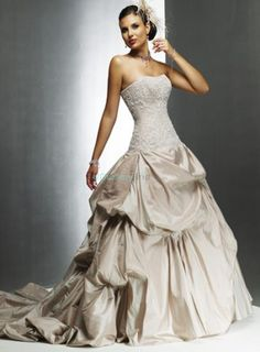 Taffeta wedding dress with corset closure and chapel train. Strapless bodice features allover lace overlay. Ball gown skirt is remarkably picked-up andruched to create an elegant look. Shown in champagne. More colors available in Color Options. Custom-to-measurement for any sizes.