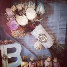 Preserved Wedding Bouquet in Shadow Box. One of my brides, Ashley Buchannan, hung her bouquet upside down after her wedding until dried. She left the lace wrapped handle with brooch and she also saved buds from her husband/mom/dad's corsage/bout, bridesmaids and saved a handkerchief from the ceremony and displayed all in a shadow box with a wooden letter from her new last name and backed it with a newspaper of her wedding date. A lovely preservation of a wedding bouquet. Well done, Ashley!