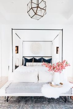 White master bedroom with iron canopy bed.