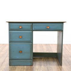 This cottage chic sewing table is featured in a solid wood with a distressed blue paint finish. This small desk has 4 drawers, shiny copper pulls and a white wood table top. Perfect for a craft room studio! #cottagechic #desks #writingdesk #sandiegovintage #vintagefurniture
