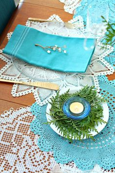 Blue holiday tablescape, winter party decor ideas. Dyed doily table runner, votive in bed of cedar.