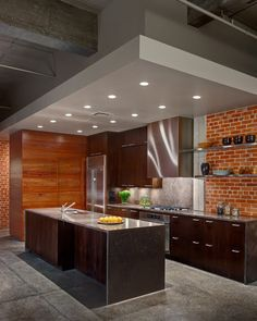 Dropped ceiling at Kitchen with clean wood cabinet + brick wall. Nice!