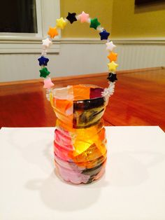 Upcycle a water bottle into a lantern with beads, pipe cleaner, flameless votive, tissue paper squares and glue. Great Girl Scout Daisy craft-use resources wisely.