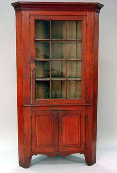 Description: Primitive corner cupboard with large cornice molding over single door with twelve glass panel door over two raised panel doors all set on cutout bracket base, 18th century.