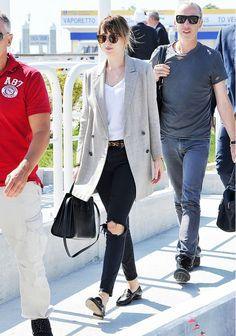 Dakota Johnson wears a v-neck t-shirt, blazer, leopard belt, distressed skinny jeans, Gucci loafers, and a Saint Laurent bag