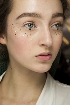 Christian Dior Spring 2017 Couture Beauty - Peter Philips adorned models' faces with metallic stars, applied in different formations around their eyes. he skipped mascara and kept lids pale to let the adornments stand out.