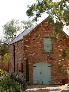 made to order vintage barn. reclaimed red bricks and the teal? door. lovely combination...I want to do this myself with all the old barns around here, why isn't anyone else doing this?