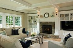 coffered ceiling,stone fireplace light color palette, casual furnishings make this room very inviting.