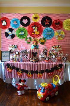 Me encanta la decoracion de esta mesa de postres de una fiesta Mickey Mouse con rosetas de papel con apliques de figuras.