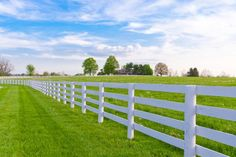 Waist height white fence with round pole style vertical posts and four horizontal widely spaced slats