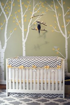 Gender-Neutral Nursery — Green Walls, White Birch Trees with Yellow Leaves — Wall Decals — Grey Birds — Bird Mobile — Grey and White Chevron Baby Crib Bedding with Yellow Accents — Grey and White flat weave rug carpet — Shana Cunningham Designs www.shanacunningham.com