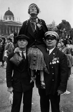 A woman sitting atop the shoulders of two men on the occasion of the coronation of King George VI, Trafalgar Square, London, England, United Kingdom, 1937, photograph by Henri Cartier-Bresson.