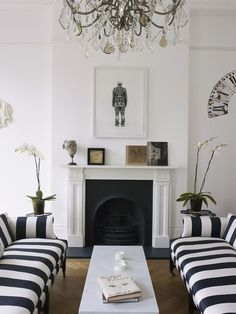 striped couches + black and white fireplace mantel + chandelier