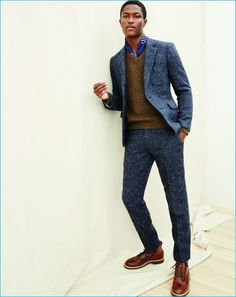 Wear a navy wool suit with a brown v-neck jumper for a classic and refined silhouette. For footwear go down the casual route with brown leather casual boots.   Shop this look on Lookastic: https://lookastic.com/men/looks/navy-suit-brown-v-neck-sweater-brown-casual-boots/23220   — Blue Print Silk Scarf  — Brown V-neck Sweater  — Navy Wool Suit  — Brown Leather Casual Boots