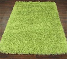 La alfombra es verde, clásica por que no tiene decoraciónes y rectangular.