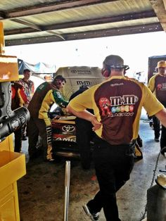 The M'S crew is busy assessing the status of the engine. Kyle Busch sits in car. 
