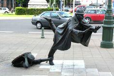 De Vaartkapoen, Bruselas, Bélgica. Hombre-jalandole-el-pie-a-otro-escultura