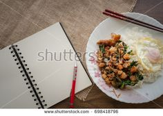 Pad Ka-prao; stir fried chopped chicken with chili and basil, served with steamed rice and fried egg on top set on wooden table with note book space for text