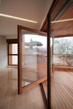 Large wood framed windows rotates open onto wooden front balcony. Studio Dwelling / cmA Arquitectos.