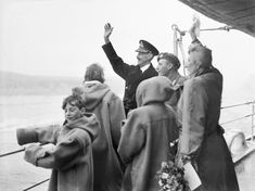 The royal family of Norway waving to the welcoming crowds from HMS NORFOLK at Oslo