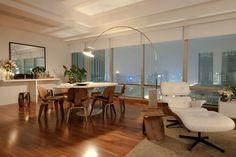 Sala maravilhosa com estar e jantar integrados e vários móveis de design assinado, como a mesa oval branca Saarinen + cadeiras de madeira Lcw + luminária Arco. Projeto Fernanda Moreira Lima, via Casa de Valentina.