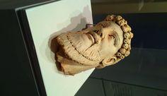 Deze kop, gemaakt van kalksteen, is zeer opmerkelijk. De baard is op Perzische wijze gehouwen, de amandelvormige ogen en de subtiele glimlach zijn juist weer typisch Grieks. De krans met eikeltjes in het haar van de man verwijst naar Zeus, de oppergod van de Romeinen. Dit laat duidelijk de handelsrelaties tussen de verschillende steden zien. Het beeldhouwwerk is gevonden in Carthago. xoxo dobec