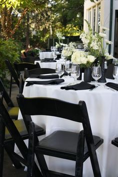 white tablecloths, black napkins, and white roses