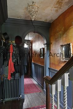 A view through an archway in a hallway with grey painted part panelling on the walls and an orange paint effect above.