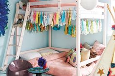 Fabulous girl's room features white bunk beds adorned with colorful metallic tassels dressed in pink linen bedding next to a gold star teepee.