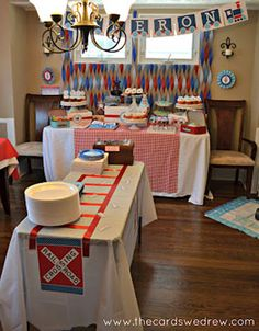 red and blue train themed choo choo first birthday party main room with train tracks for table cloths