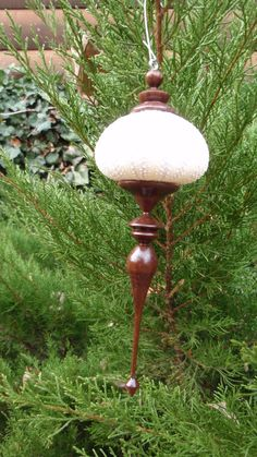 """This ornament is made with a real Purple Sea Urchin shell and Black Walnut wood. The delicate finial was carefully turned and sanded on a lathe until very smooth, then finished with three coats of tung oil to make it shine. A combination of the forest and sea waiting for that special tree. Because of material variations, the size may vary between 1 1/4"""" -2"""" wide by 5""""-7"""" long."""