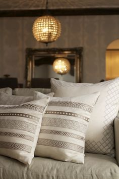 Interior designers often come to us looking for warming accessories, to add interest to a scheme. Neutral colours are versatile, but it's important to incorporate high quality fabrics and plenty of texture and embellishment to achieve an inviting ambience. Our linen Moulin cushions, pictured, are hand-finished with silk embroidery, which has a subtly reflective quality that interacts beautifully with candlelight, enhancing the cosy glow.