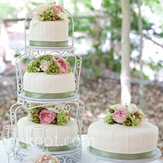 Wrought-iron cake stands supported the cakes which were decorated with sage green ribbon and soft pink and green blooms.