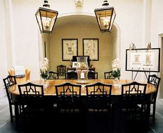 Dining Room - A pair of black lanterns suspended over a wooden table and black chairs