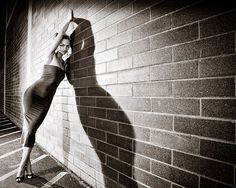 Sexy tube top dress, stunning black and white portrait, gritty low key lighting, woman posing on a brick wall
