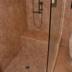 small walk-in shower with bench and glass enclosure