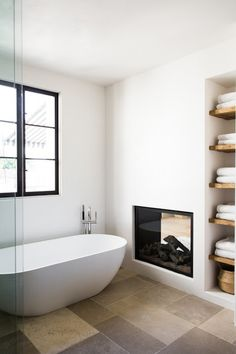 Bathroom with Old World European style: limestone floor tiles, modern see through fireplace, black wood windows, salvaged wood shelves, plaster walls, and freestanding modern tub. Interior Design Inspiration: European Villa in West Hollywood - Hello Lovely
