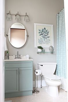 Like the light grey wall color and agua green/white accents, shower curtain idea.  Light fixture, mirror, shelf/pic idea. downstairs bath.