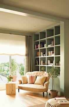 En la biblioteca Sofá antiguo, en Mavi Lizán. Mesa y cojín de rayas, en Luzio. Lámpara de Home Design.