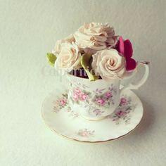 Taza con bizcocho y crema de chocolate con flores y mariposas en azúcar