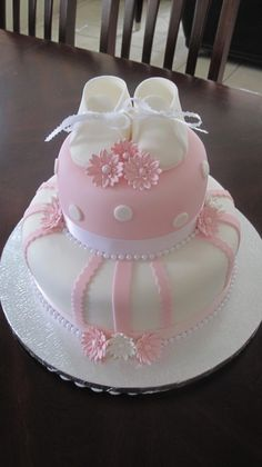 Baby shower cake - cake is covered in an ivory & baby pink fondant, and topped with gumpaste booties & daisies. Misschien leuk als dooptaart :-) Torta Baby Shower, Baby Shower Kuchen, Tortas Baby Shower Niña, Baby Shower Pasta, Baby Shower Parties, Pretty Cakes, Cute Cakes, Beautiful Cakes, Baby Girl Cakes