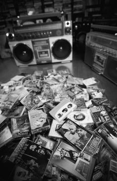 Pile of cassette tapes in front of two boomboxes.